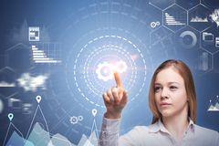 Businesswoman using infographics interface, gears. Businesswoman in white shirt using gear hud interface with infographics hologram. Toned image double exposure stock photography