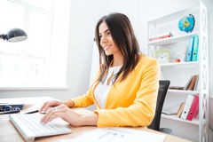 Businesswoman using keyboard and computer mouse in office Stock Image