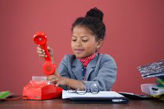 Businesswoman using land line phone. While working at desk against orange background Royalty Free Stock Photo