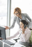 Businesswoman using landline phone while manager pointing towards computer in office Stock Photography