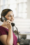 Businesswoman Using Landline Phone In Office Stock Photo