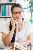 Businesswoman using landline phone in office Royalty Free Stock Photos