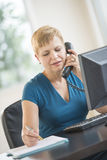Businesswoman Using Landline Phone While Working At Desk Royalty Free Stock Photo