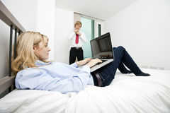 Businesswoman using laptop in bed with businessman adjusting tie at hotel Royalty Free Stock Images
