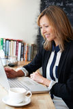 Businesswoman Using Laptop In Cafe. Businesswoman Uses Laptop In Cafe Royalty Free Stock Image