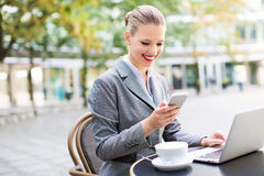Businesswoman using laptop at cafe Royalty Free Stock Images