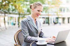 Businesswoman using laptop at cafe Royalty Free Stock Photos