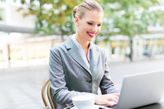Businesswoman using laptop at cafe Stock Photo