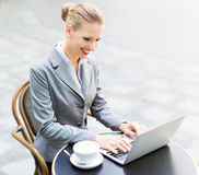 Businesswoman using laptop at cafe Stock Images