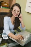 Businesswoman Using Laptop Cell Phone and PDA portrait Royalty Free Stock Image