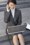Businesswoman Using Laptop And Cellphone Outdoors Royalty Free Stock Photos