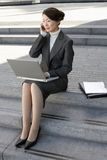 Businesswoman Using Laptop And Cellphone Outdoors Royalty Free Stock Photo