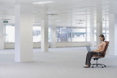 Businesswoman Using Laptop On Chair In Empty Office Stock Image