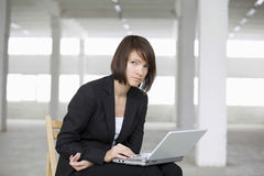 Businesswoman Using Laptop On Chair In Empty Warehouse Stock Photos