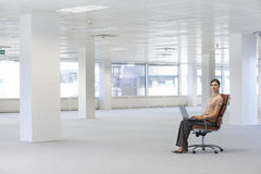 Businesswoman Using Laptop On Chair In Office Stock Photos