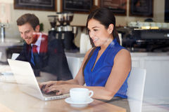 Businesswoman Using Laptop In Coffee Shop Royalty Free Stock Images