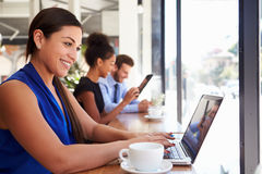 Businesswoman Using Laptop In Coffee Shop Stock Photography