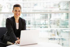 Businesswoman using laptop computer looking to camera Stock Photography