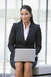 Businesswoman using laptop computer outside. Building Royalty Free Stock Photos