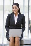Businesswoman using laptop computer outside. Building Stock Images