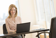 Businesswoman Using Laptop At Desk In Office Stock Image