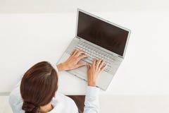 Businesswoman using laptop at desk Stock Image
