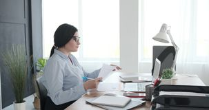Businesswoman using laptop while doing paperwork at office. Businesswoman working on laptop while doing paperwork at office desk stock footage