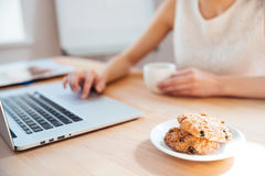 Businesswoman using laptop and drinking coffee with cookies on workplace Stock Photography
