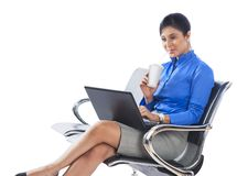 Businesswoman using laptop and drinking soft drink Stock Photography