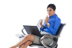 Businesswoman using laptop and drinking soft drink Stock Images