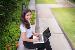 Businesswoman using laptop in garden outdoor to work at home, Co. Businesswoman using laptop in garden outdoor to work at home., Computer and electronic concept stock photography