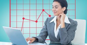 Businesswoman using laptop with graph in background Stock Images