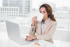 Businesswoman using laptop at her desk and drinking coffee Royalty Free Stock Image