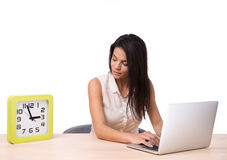 Businesswoman using laptop and looking on clock Stock Images