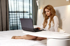 Businesswoman using laptop while lying on bed Royalty Free Stock Images