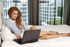 Businesswoman using laptop while lying on bed Royalty Free Stock Photo