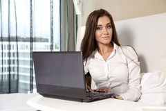 Businesswoman using laptop while lying on bed Royalty Free Stock Photos