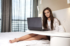 Businesswoman using laptop while lying on bed Stock Images
