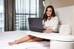 Businesswoman using laptop while lying on bed Stock Photos