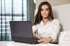 Businesswoman using laptop while lying on bed Royalty Free Stock Photography