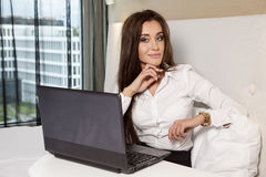Businesswoman using laptop while lying on bed Royalty Free Stock Image