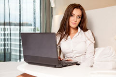 Businesswoman using laptop while lying on bed Stock Image