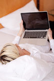 Businesswoman Using Laptop While Lying On Bed Stock Photography