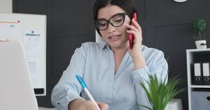 Businesswoman talking on phone while working at office. Businesswoman using laptop and mobile phone while doing paperwork at office stock video footage