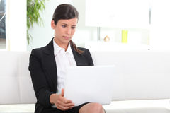 Businesswoman using laptop in office Stock Photos