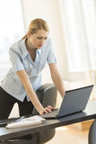 Businesswoman Using Laptop At Office Desk Stock Image