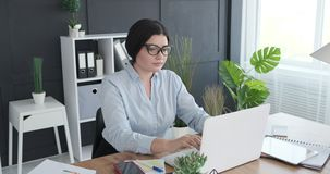 Businesswoman using laptop at office. Businesswoman working on laptop at office desk stock video footage