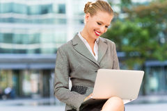 Businesswoman using laptop outdoors Royalty Free Stock Images