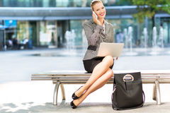 Businesswoman using laptop outdoors Royalty Free Stock Photos
