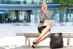 Businesswoman using laptop outdoors Royalty Free Stock Image